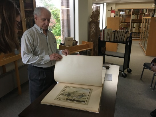 ENGL WRIT 2223 Librarian Peter Glenister displaying oversized book