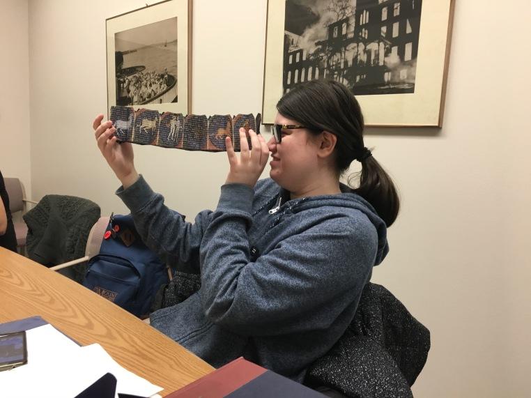 ENGL WRIT 2223 student Corrine MacLean examining a book